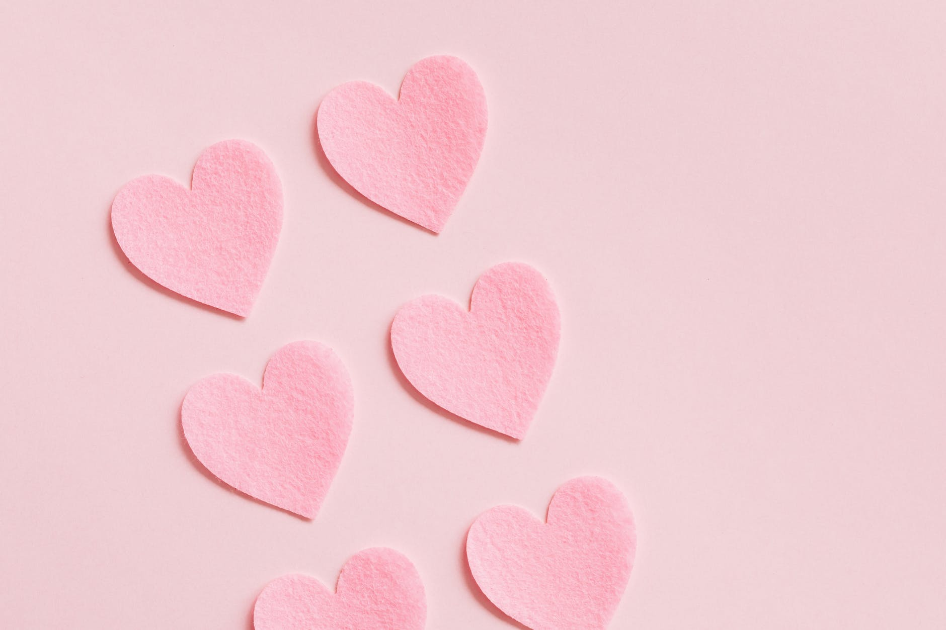 heart shaped paper cutouts on pink background